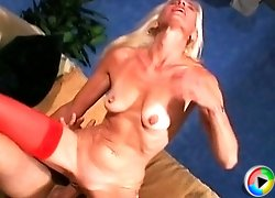 Sporty blonde granny in sexy red stockings gives head, rides cock and gets fucked from behind