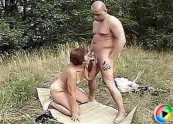 Granny in glasses gives guy a killer blowjob outdoors and lets him finger her wet crack